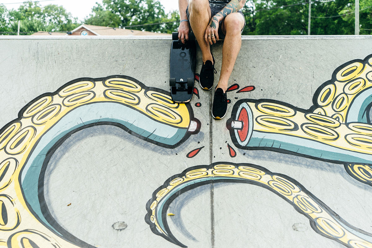 Skateboarder sitting on wall with octopus graffiti mural